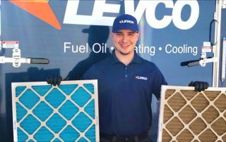 a Levco technician holding a clean and a dirty air filter