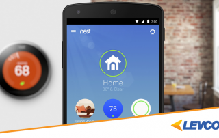 Nest app open on a smart phone and the nest thermostat on the wall.